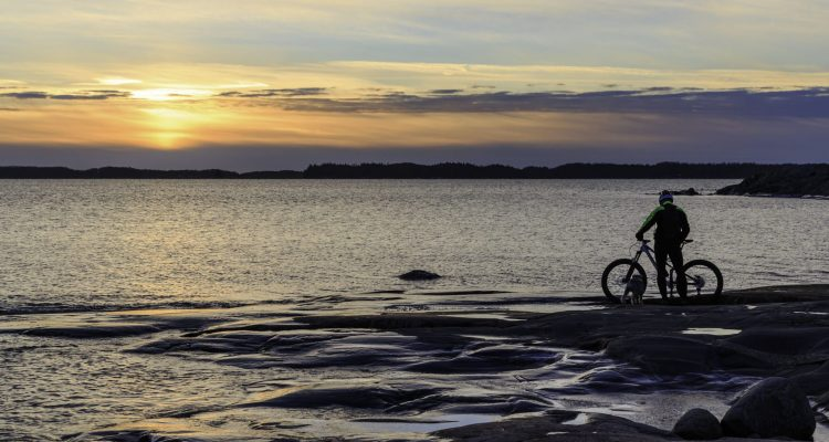 Cyclist admiring the sunset in Kopparnäs
