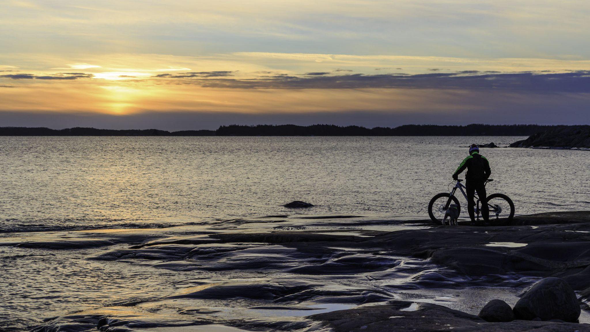 Cyclist admiring the sunset in Kopparnäs
